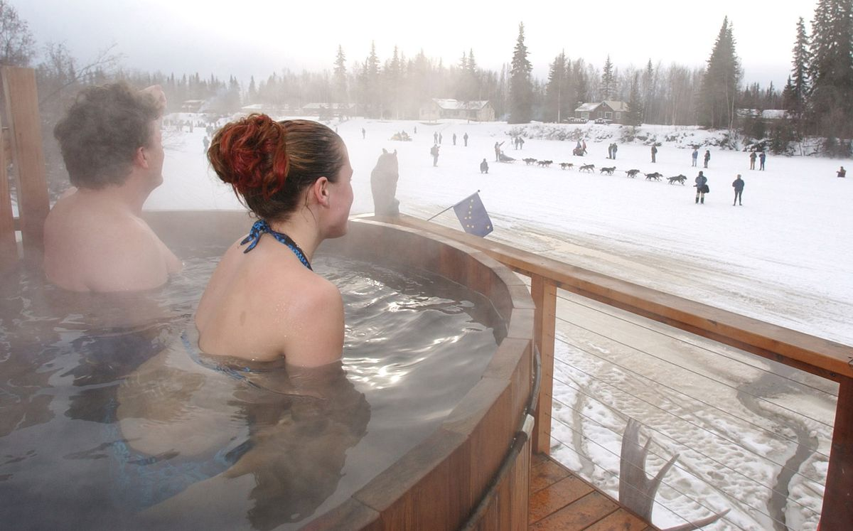 Fans in Fairbanks watch Iditarod mushers cruise by from a hot tub built on a platform overhanging the Chena River at the 2003 race. (Erik Hill / ADN archive)