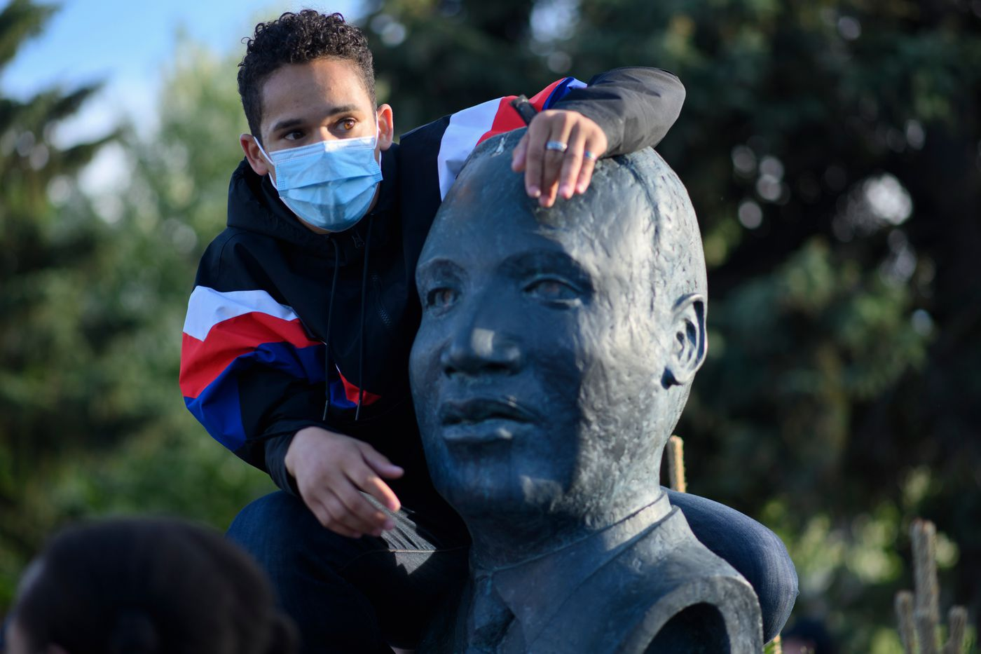 Protest organizer Amable Rosa holds on to the Martin Luther King likeness. (Marc Lester / ADN)