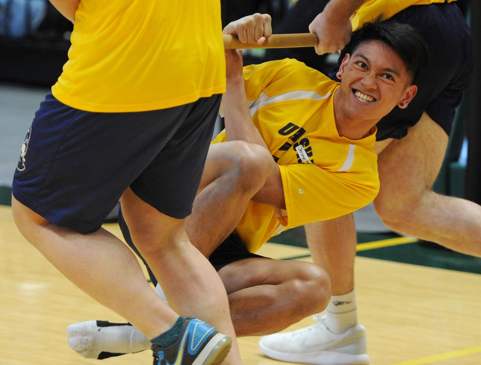 Jerome Molina, 17, of Unalaska grimaces as he hangs on during a first-place performance in the boys wrist carry event at the Native Youth Olympics on Thursday, April 24, 2019. (Bill Roth / ADN)