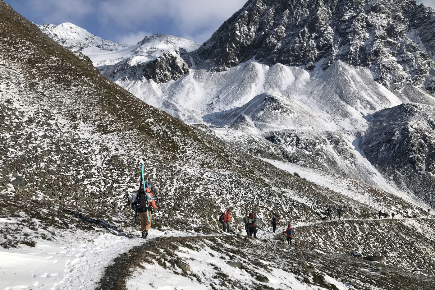 OCTOBER 17. Skiers and hikers descend out of the Crow Pass area. Dozens of skiers hiked to glaciers above Crow Pass to test the new snow. Some skiers reported just 3 inches of new snow on top of the old snow and ice of the glaciers. (Anne Raup / ADN)