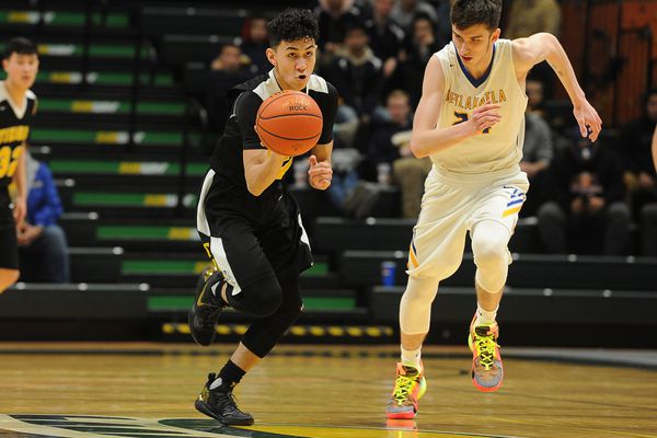 Tikigaq's Jalen Cannon drives down the court as Metlakatla's Aiden Rolando purses in the Class 2A boys state basketball championship game at the Alaska Airlines Center on Saturday, March 16, 2019. (Photo by Bob Hallinen)