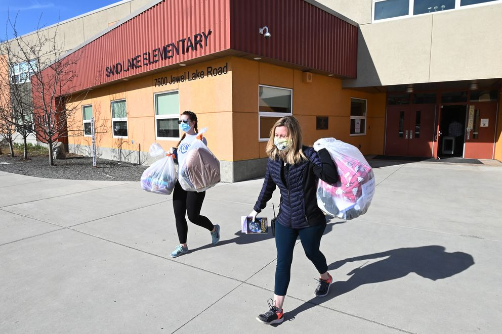 Teachers Kirstin Barboza, left, and Hali Tuomi carry bags with personal belongings to students waiting in vehicles at Sand Lake Elementary on Tuesday, May 5, 2020, during the COVID-19 pandemic. (Bill Roth / ADN)