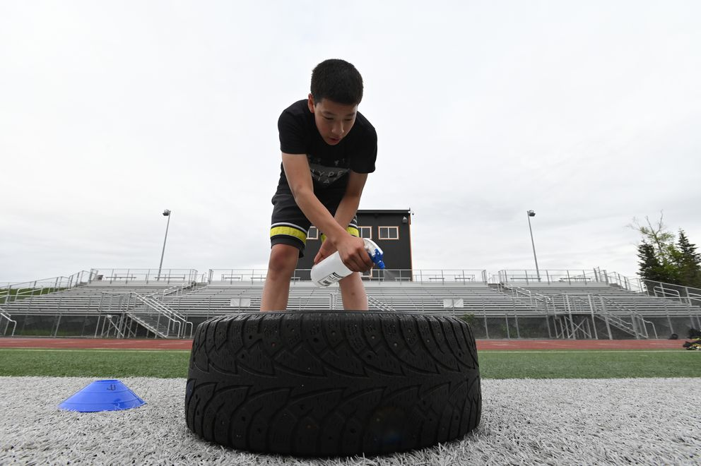 Freshman Joe Weber-Thomas disinfects a tire as the South High Wolverines took to the field for high intensity interval training on the first day of football practice on Monday, June 8, 2020. (Bill Roth / ADN)