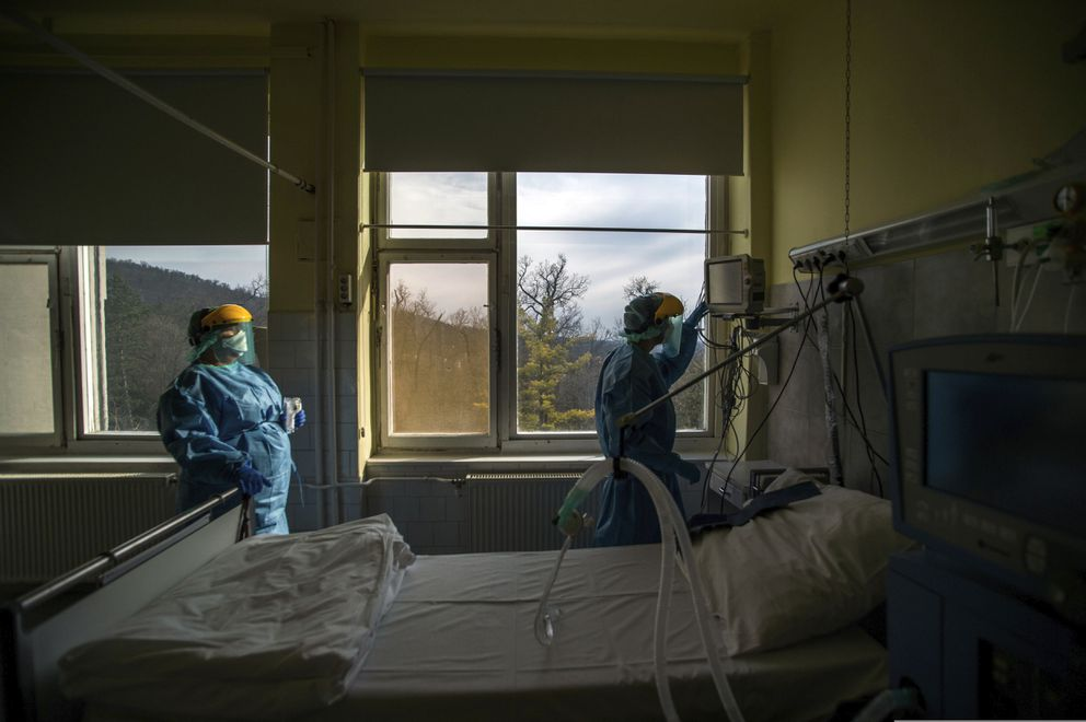 FILE - In this March 24, 2020, file photo, medical staff members check a ventilator in protective suits at the care unit for the new COVID-19 infected patients inside the Koranyi National Institute of Pulmonology in Budapest. (Zoltan Balogh/MTI via AP, File)