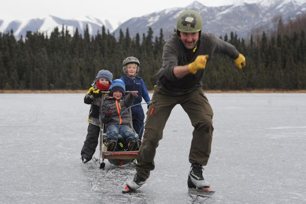 Tony Fischbach ice skates across the frozen surface of Goose Lake while pulling six-year-old's Graham Coons, Henry Couvillion, and Ketch Fischbach, as they ride a kick sled