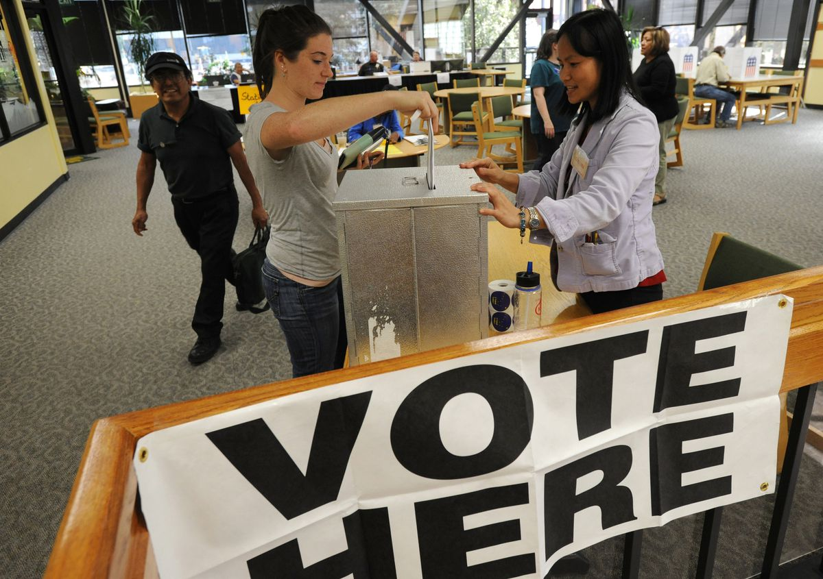 Election worker Lovelyn Marquez, right, watches as Kat Sweetman casts her ballot on the second floor of the UAA Student Union on Monday, August 18, 2014. (Bill Roth / ADN)
