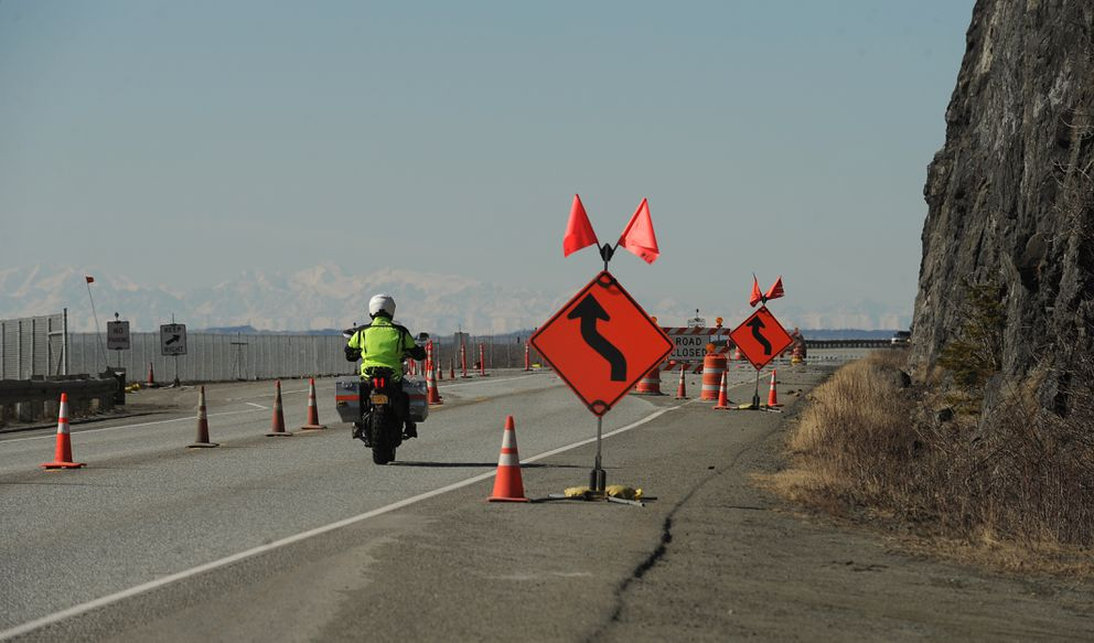 A motorcycle passes by a cliff face along the Seward Highway next to Turnagain Arm on Wednesday. Traffic has been moved over this spring to avoid falling ice and rock. (Bob Hallinen / Alaska Dispatch News)