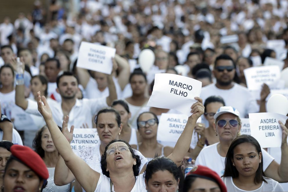 In this Feb. 1, 2019 file photo, friends and relatives hold signs with the names of victims, during a march paying homage to the victims of a mining dam collapse one week prior in Brumadinho, Brazil. (AP Photo/Andre Penner, File)