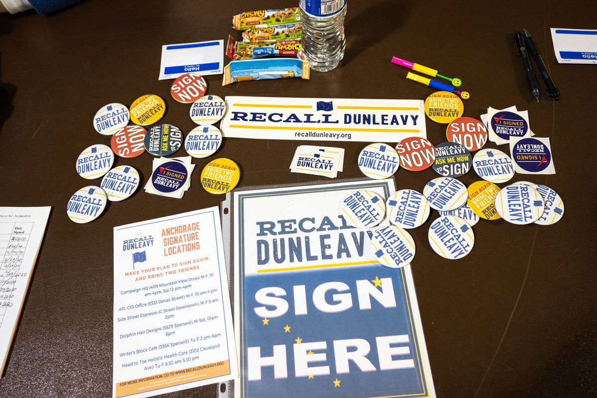 Buttons and stickers are displayed on a table set up by the Recall Dunleavy group on Saturday, Feb. 29, 2020 at the Sullivan Arena in Anchorage. The group is beginning its second round of signature-gathering for a vote to recall Gov. Mike Dunleav. (Loren Holmes / ADN)