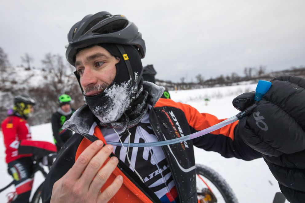 David Arteaga shows his frozen hydration tube after racing 43 miles in temperatures that hovered around zero degrees. (Loren Holmes / ADN)