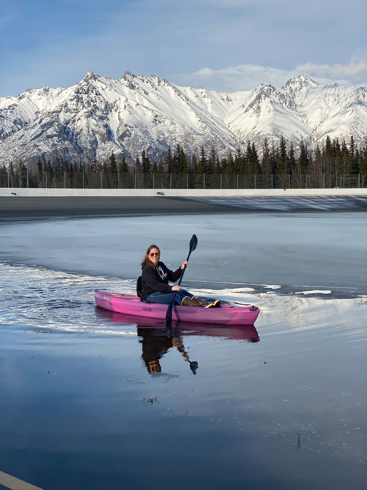 Alaska Raceway Park owner Michelle Lackey Maynor kayaks across track's infield last month after snow melted at the Palmer track. The water is gone and the track is ready for season-opening races Sunday. (Photo by Don Maynor)