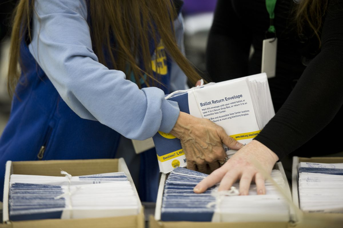 Election workers Bonnie Jack, left, and Ember Jackinsky place ballot envelopes in boxes for storage on April 5, 2019 at Anchorage's Election Center. (Marc Lester / ADN)
