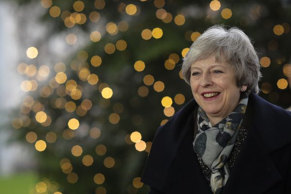 In this Dec. 11, 2018 photo British Prime Minister Theresa May smiles in front of a Christmas tree when arriving for a meeting with German Chancellor Angela Merkel at the chancellery in Berlin. (AP Photo/Markus Schreiber)
