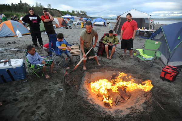 In a July 2014 file photo, Justin Ching tends to a campfire in the sand while dipnetting at the mouth of the Kenai River. The city of Kenai is seeking to build a road to provide personal use anglers access to the popular dipnetting spot wihout crossing private property.