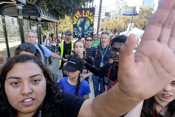 Climate activist Greta Thunberg, center with hat, is escorted after she participated in a student-led climate change march in Los Angeles on Friday, Nov. 1, 2019. (AP Photo/Ringo H.W. Chiu)