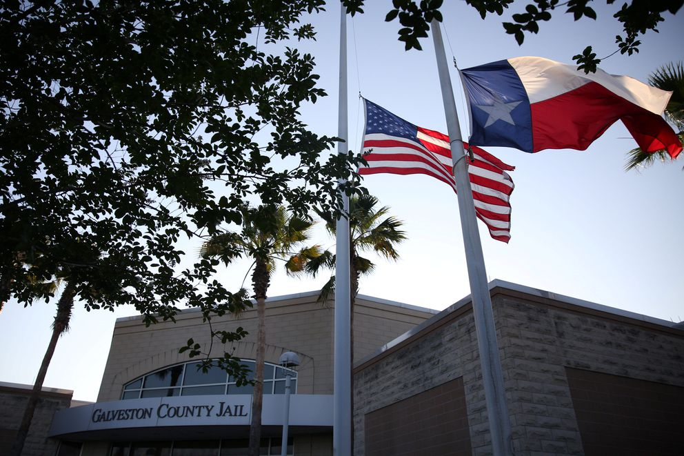 Flags fly at half mast outside the Galveston County Jail in Galveston, Texas, U.S., where suspect Dimitrios Pagourtzis was charged in connection with a shooting that left several people dead at Santa Fe High School in Santa Fe, Texas, U.S., May 18, 2018. REUTERS/Pu Ying Huang