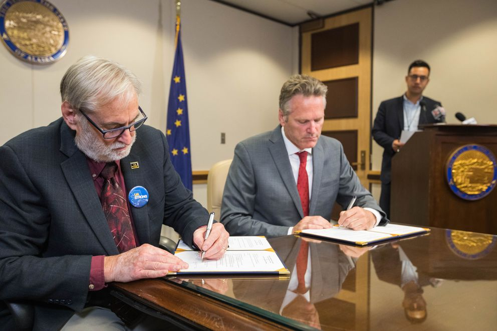 UA Board of Regents chairman John Davies and Gov. Mike Dunleavy sign an agreement for a 3-year, $70 million budget cut to the University of Alaska, on Tuesday, Aug. 13, 2019 at the governor's conference room in Anchorage. Dunleavy had originally vetoed $130 million in state funding for UA for the current fiscal year that started July 1, atop a $5 million cut approved by the Legislature. (Loren Holmes / ADN)