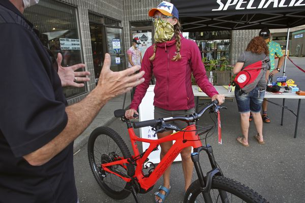 Pepper Cook, an employee at The Bicycle Shop in Anchorage, talks with a customer outside the shop on Aug. 7, 2020. (Emily Mesner / ADN)