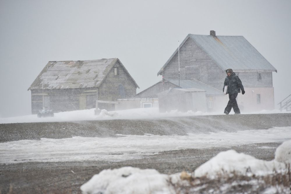 A pedestrian walks into the wind in Gambell on April 25, 2017. (Marc Lester / Alaska Dispatch News)