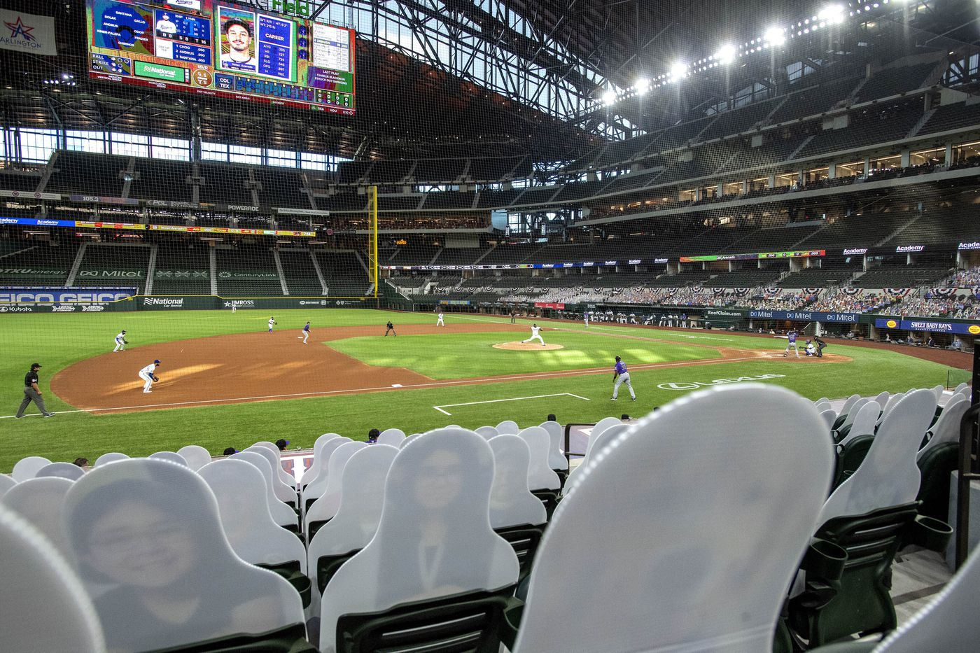 The Texas Rangers and the Colorado Rockies play in front of cardboard cutouts depicting fans, dubbed 'DoppleRangers, ' during the first inning of an opening day baseball game Friday, July 24, 2020, in Arlington, Texas. (AP Photo/Jeffrey McWhorter)