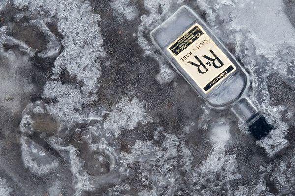 An empty bottle of Rich and Rare whiskey is froze into the surface of Campbell Creek on Saturday, December 13, 2014.