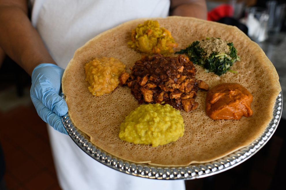 Dawit Ogbamichael holds a doro tibs platter, a chicken dish served on injera, a flatbread, with other sides. Queen of Sheba Ethiopian restaurant is located on Dawson Street near Benson Boulevard in Midtown Anchorage. Photographed on May 2, 2019. (Marc Lester / ADN)