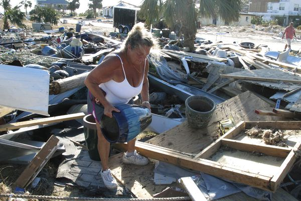 In this Oct. 14, 2018 photo Dena Frost salvages an unbroken clay pot from the wreckage of her pottery business in Mexico Beach, Fla. For decades, the town has persisted as a stubbornly middlebrow enclave on what residents proudly refer to as Florida's
