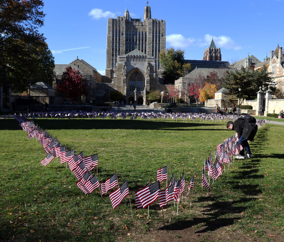 Eighteen-year-old political science major Elias Mastakouris of Long Island replants American flags that had blown over in front of Sterling Library at Yale University on Veterans Day. (Photo for The Washington Post by Stan Godlewski)