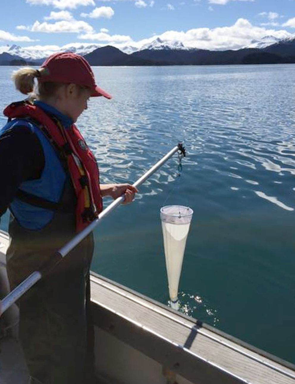 Rosie Robinson with Kachemak Bay National Estuarine Research Reserve does a plankton tow to monitor for harmful algal species in the bay last August. (Kachemak Bay National Estuarine Research Reserve)