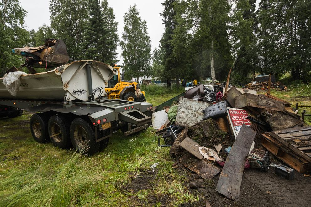 A crew from A-1 Lawn and Landscaping clears debris from a property north of Huffman Road on Wednesday. (Loren Holmes / ADN)