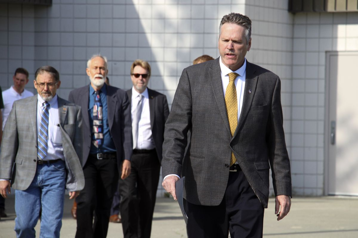FILE - This June 14, 2019 file photo shows Alaska Gov. Mike Dunleavy leading state and local officials out of Wasilla Middle School in Wasilla, Alaska, to a news conference. State lawmakers have rejected Dunleavy's suggested location for a special session. House Speaker Bryce Edgmon and Senate President Cathy Giessel issued a joint statement Monday, June 24, 2019 saying they will convene July 8 in Juneau and hold most hearings in Anchorage. Dunleavy had called the session for Wasilla, his hometown and conservative base.(AP Photo/Mark Thiessen, File)