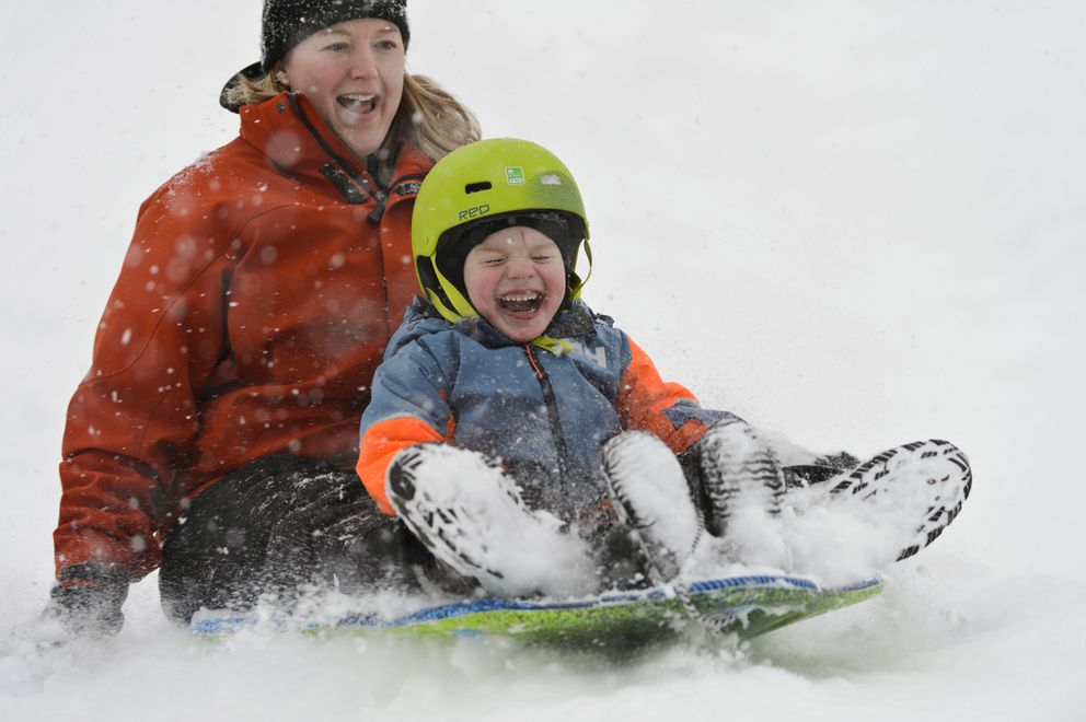 Lindsey Shippen and her son Lyle, 3, ride down the Russian Jack Springs Park hill. (Marc Lester / ADN)