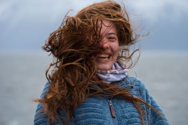 Wind whips the hair of Savannah Stone, 16, as she visits Beluga Point on Turnagain Arm during a windstorm on May 10, 2019. (Marc Lester / ADN)
