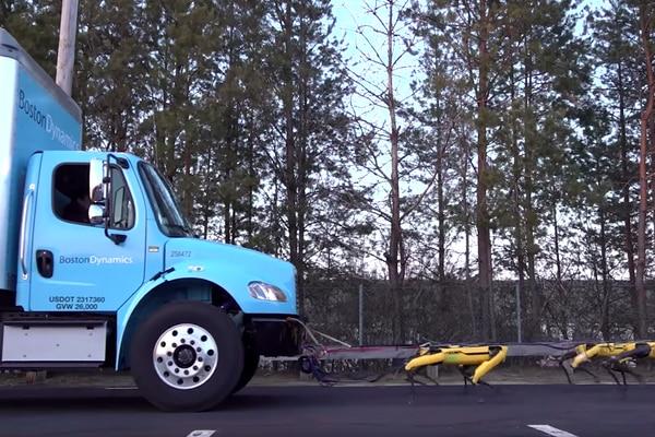 SpotMini robot dogs pull a Boston Dynamics truck up a slight incline. (Boston Dynamics handout)