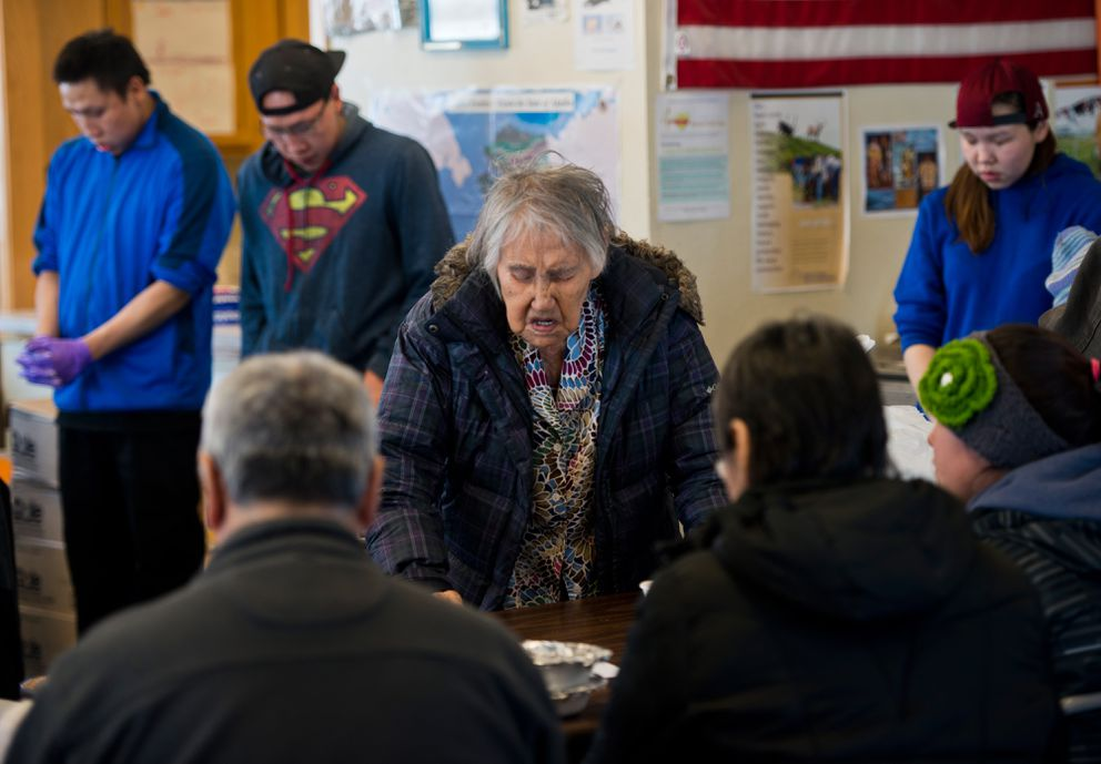 Barbara Kogassagoon, center, gives a closing prayer at the celebration event. The Native Village of Savoonga hosted a community appreciation dinner to honor Savoonga's seven community health aides on Thursday. (Marc Lester / Alaska Dispatch News)