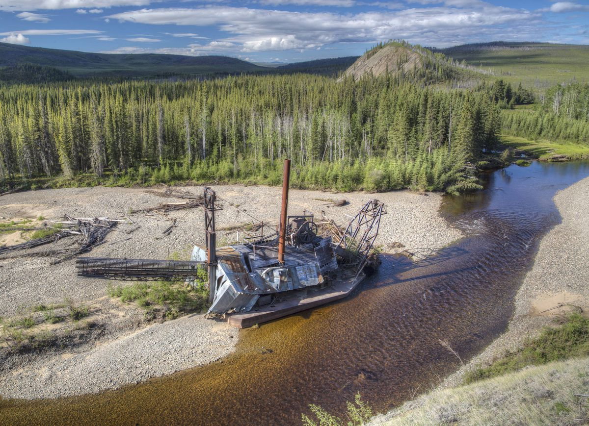 The abandoned works of a gold mining operation are seen along the Fortymile River in eastern Alaska. A nonprofit is working with placer miners in the area to reclaim gold for companies such as Apple and Tiffany from old tailings as well as restore vegetation along the river banks. (Bob Wick/Bureau of Land Management)