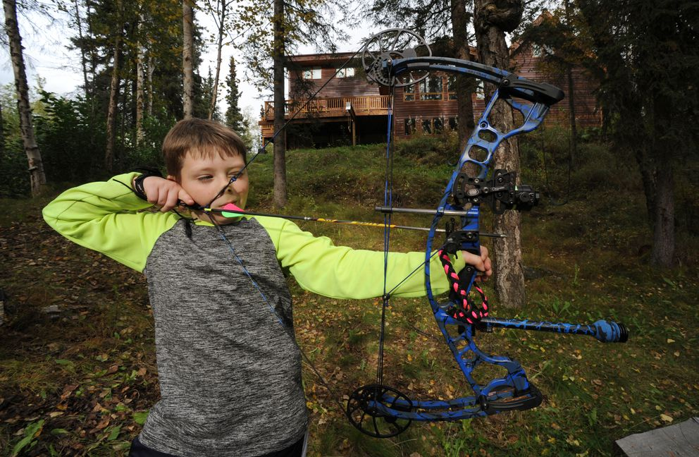 Cole Stoddard, 9, takes aim at a target set up in the woods near his families Anchorage hillside home on Monday, Sept. 12, 2016. (Bill Roth / Alaska Dispatch News)