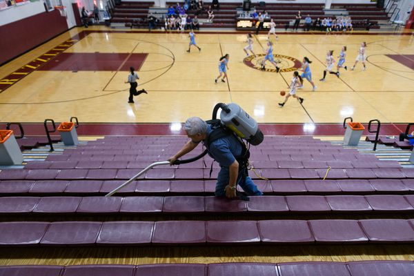 Grace Christian School maintenance employee Florenzio Roserio cleans the empty stands as the Dillingham and Bristol Bay girls basketball teams play in the Class 2A Great Alaska Conference tournament on Friday, March 13, 2020. Fans were not allowed to attend the games on Friday due to coronavirus concerns. (Marc Lester / ADN)