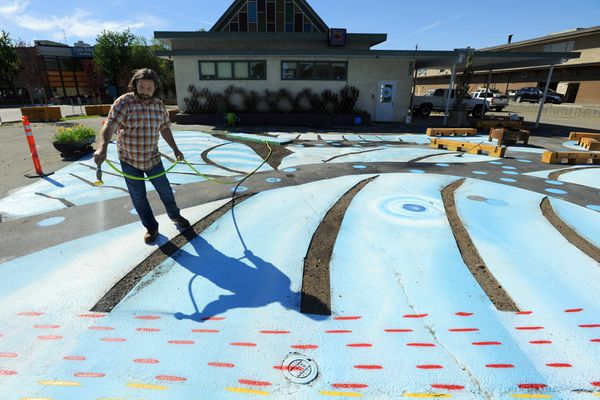 Chad Taylor of Intrinsic Landscapes hoses off a horizontal mural by artist Kerby McGhee after strips of asphalt have been removed on Friday afternoon, August 4, 2017, at the Church of Love in Spenard. The mural is designed to reimagine the space for people rather than for vehicles. Flowers and grasses have been planted in what is now titled