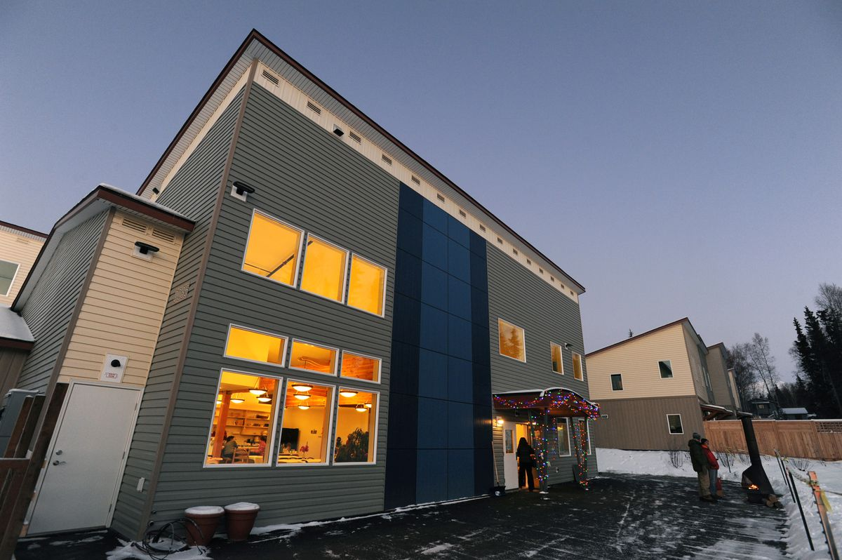 Warm light radiates from the common house windows as the sun sets on Dec. 11. Ravens' Roost is Anchorage's first cohousing community of privately owned homes designed for neighbors to get to know one another. (Bill Roth / Alaska Dispatch News)