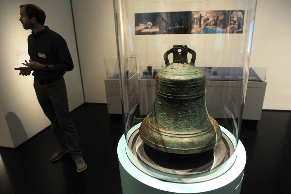Ryan Kenny, associate director, exhibitions at the Anchorage Museum stands near the first artifact to be raised from the HMS Erebus was this bronze bell on display in the Death in the Ice: The Mystery of the Franklin Expedition exhibit on Thursday, June 6, 2019. (Bill Roth / ADN)