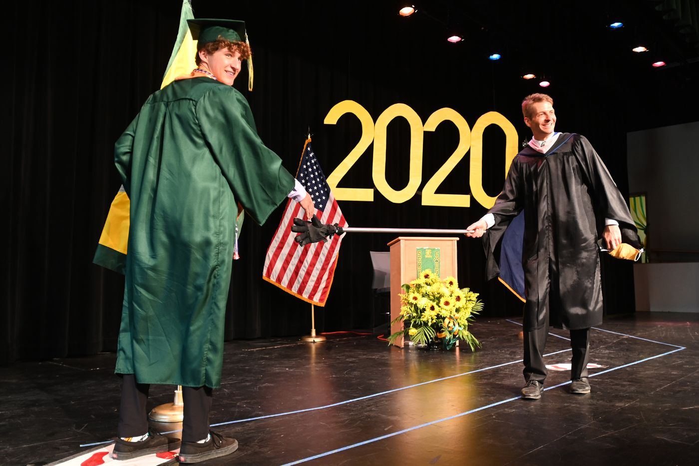 Service High School graduating senior Carter Christopherson pretends to shake hands with principal Frank Hauser while keeping social distancing after he walked across the stage on Tuesday, May 19, 2020. Christopherson, who was named captain of the soccer team for a season that never happened because of the COVID-19 pandemic, will be attending University of Colorado, Colorado Springs. (Bill Roth / ADN)