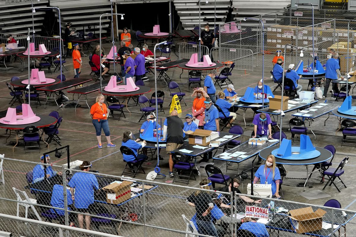 In this May 6, 2021 file photo, Maricopa County ballots cast in the 2020 general election are examined and recounted by contractors working for Florida-based company, Cyber Ninjas at Veterans Memorial Coliseum in Phoenix. (AP Photo/Matt York, Pool, File)