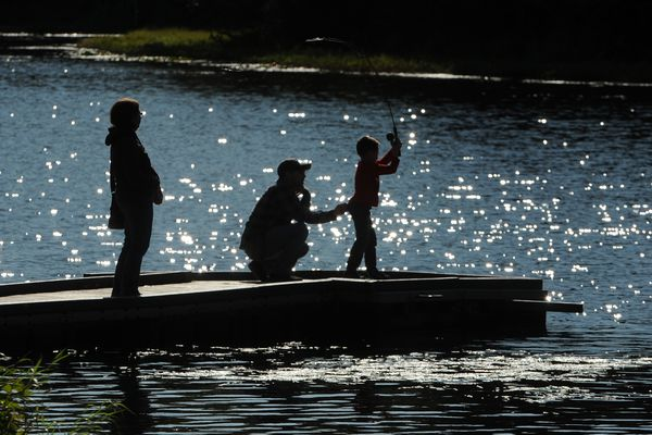 As stepmom April Wright looks on Ralph Sara guides his son, Aiden Sara, as he casts into Little Campbell Lake in Kincaid Park in Anchorage, AK on Saturday, Sept 1, 2018. (Bob Hallinen / ADN)