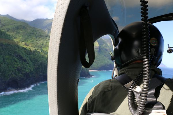 This photo provided by the Hawaii Department of Land and Natural Resources shows a Coast Guard search and rescue team looking over Napali Coast State Wilderness Park for a tour Helicopter that disappeared in Hawaii with seven people aboard on Friday, Dec. 27, 2019. Authorities say the helicopter's owner called for help about 45 minutes after the chopper was due back from a tour of Kauai's Na Pali Coast on Thursday evening. (Dan Dennison/Hawaii DLNR via AP)