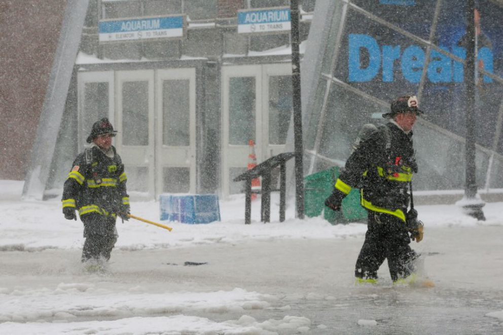 Boston firefighters wade through a street floodedby tidal surge. REUTERS/Brian Snyder