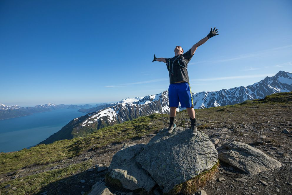 Ben Schultz celebrates reaching the top of the Mt. Marathon race course Wednesday, June 19, 2019 in Seward. Schultz, an Anchorage firefighter, fell from a ladder during a training accident in 2017 and is running the race as part of his recovery from the accident, which left him with a traumatic brain injury. Schultz climbed the steep, technical trail for the first time Wednesday with fellow firefighter and race veteran Rob Whitney. (Loren Holmes / ADN)