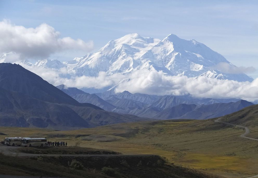 In this Aug. 26, 2016, file photo sightseeing buses and tourists are seen at a pullout popular for taking in views of Denali. (AP Photo/Becky Bohrer, File)