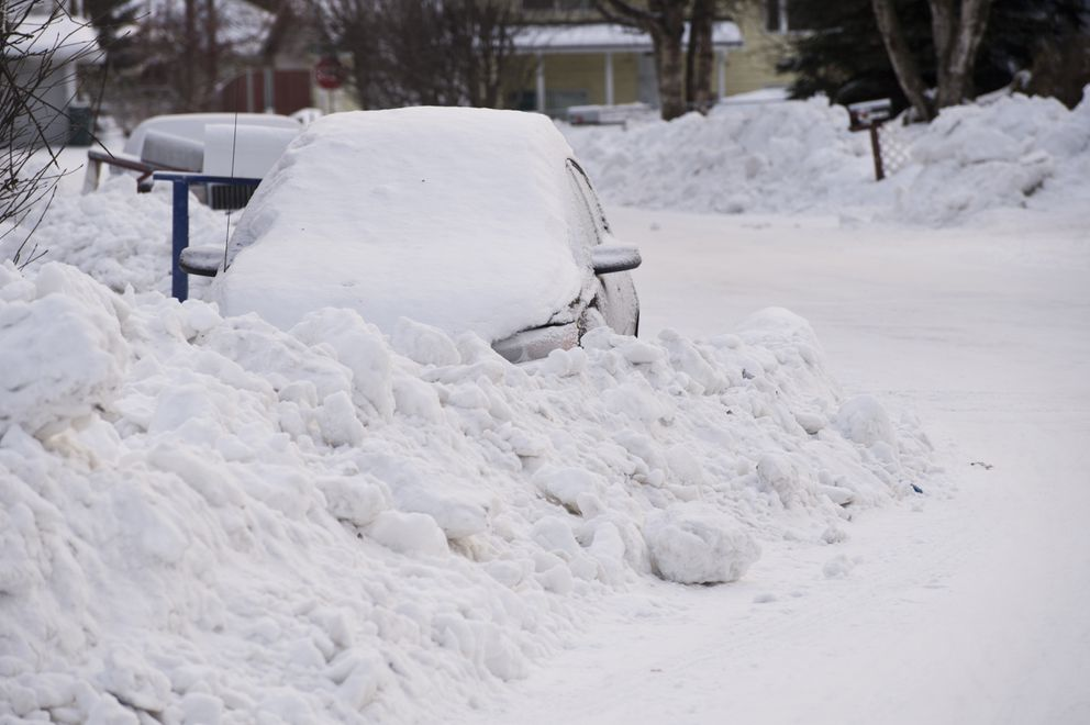A snow berm is plowed around vehicle parked on the road of a residential Spenard neighborhood on January 11, 2019. (Marc Lester / ADN)