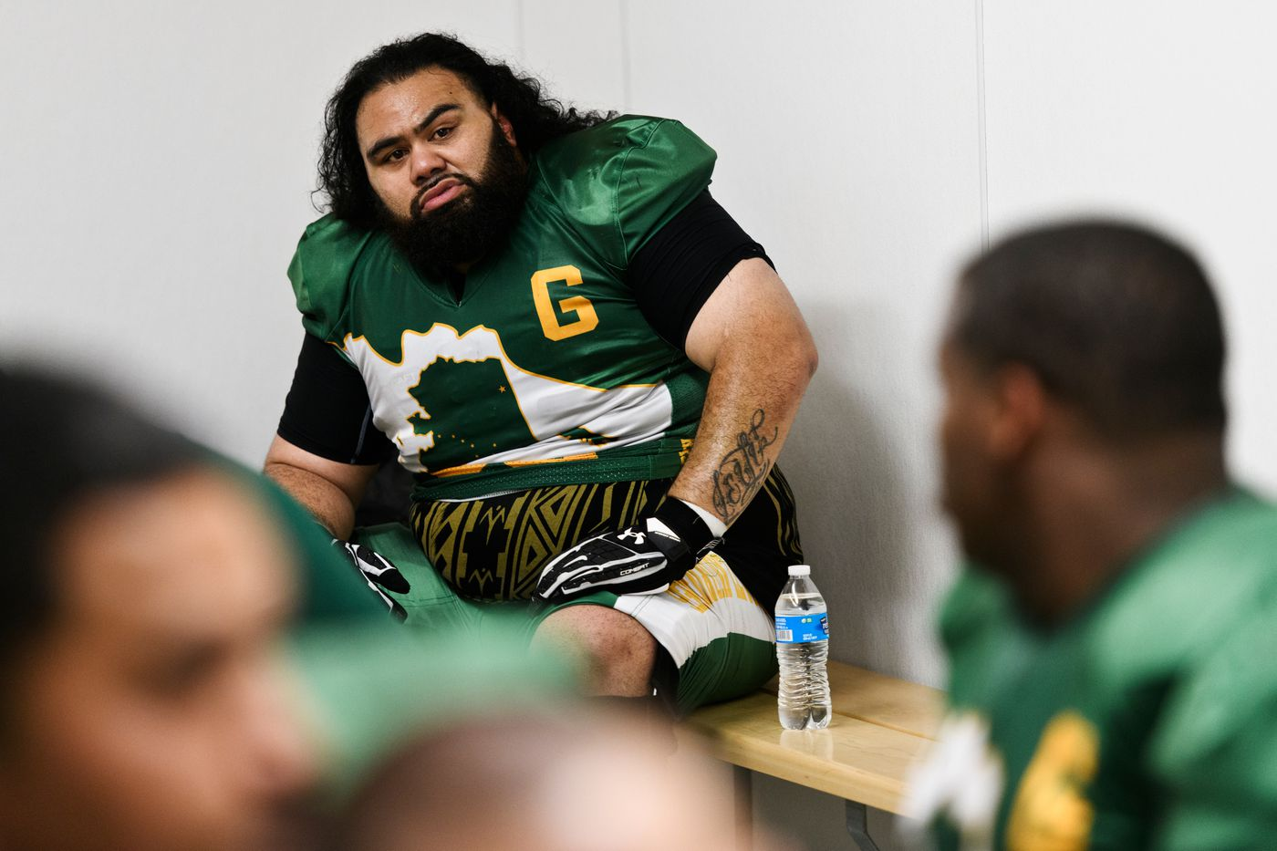 Demetrius Lalofau talks with a coach in the locker room at halftime of a game against the Anchorage Cowboys on Sept. 3, 2018. (Marc Lester / ADN)